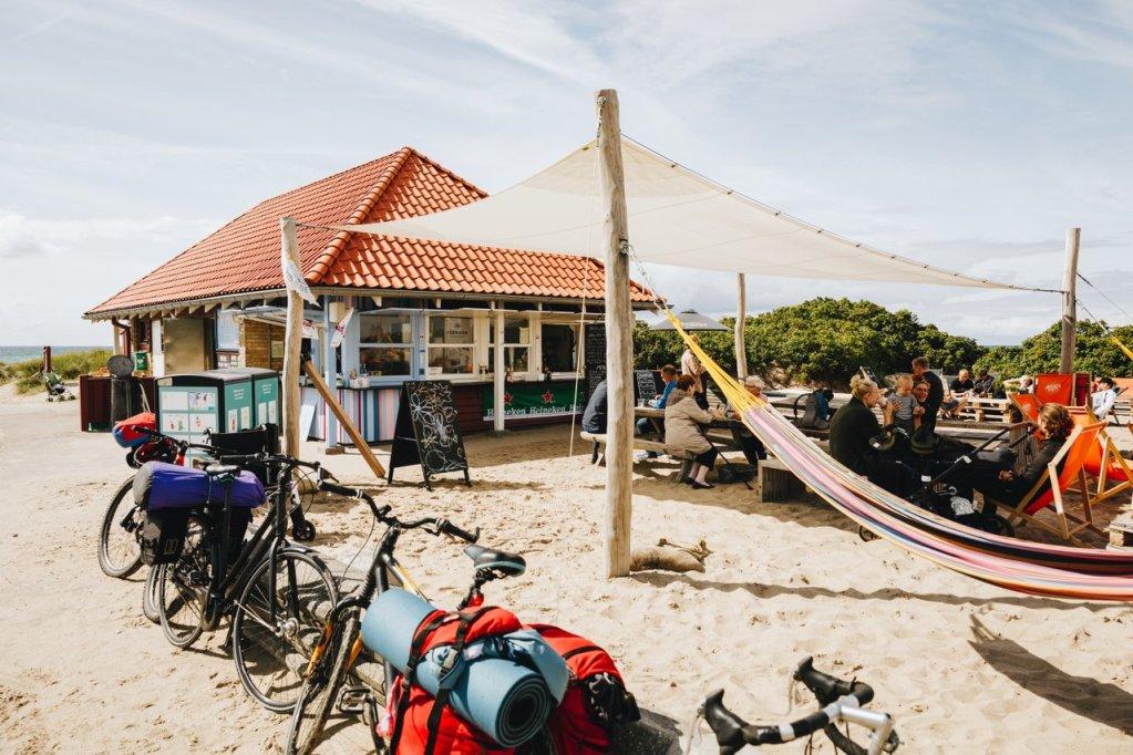 Mange parkerte sykler utenfor en koselig strandkafe. Solseil og hengekøyer og uteservering.