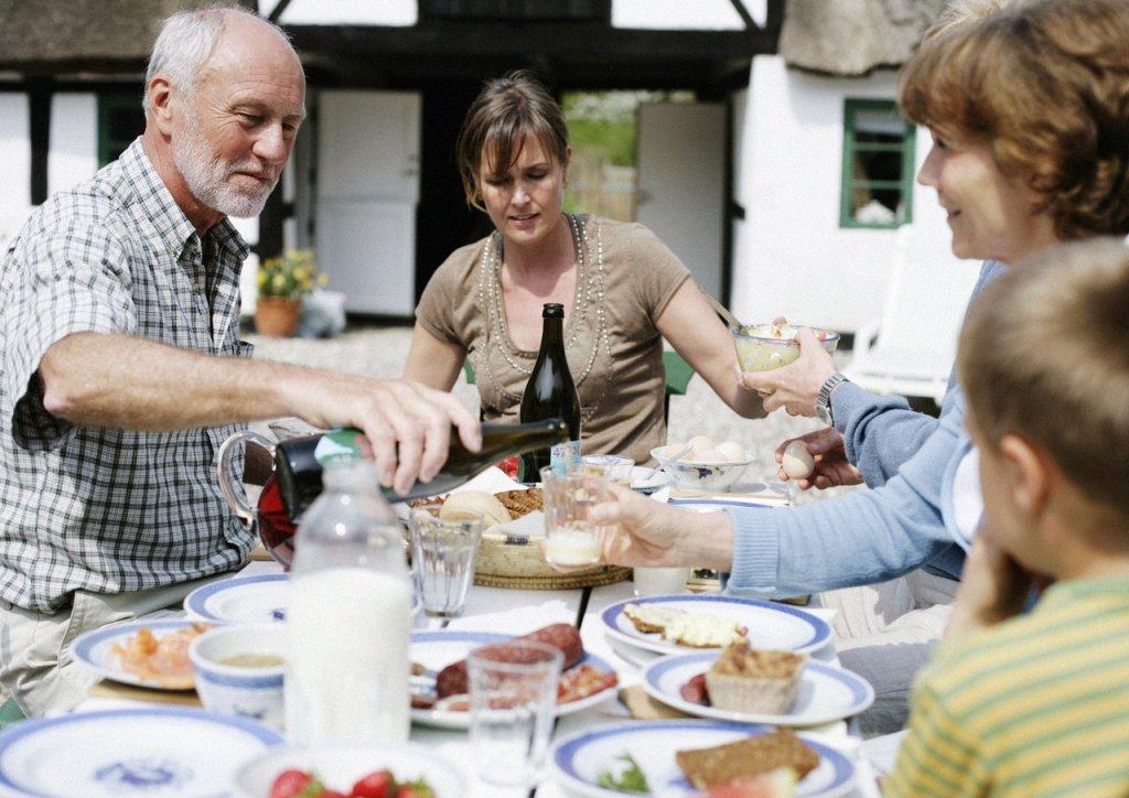 Familie på tre generasjoner spiser felles måltid utendørs.