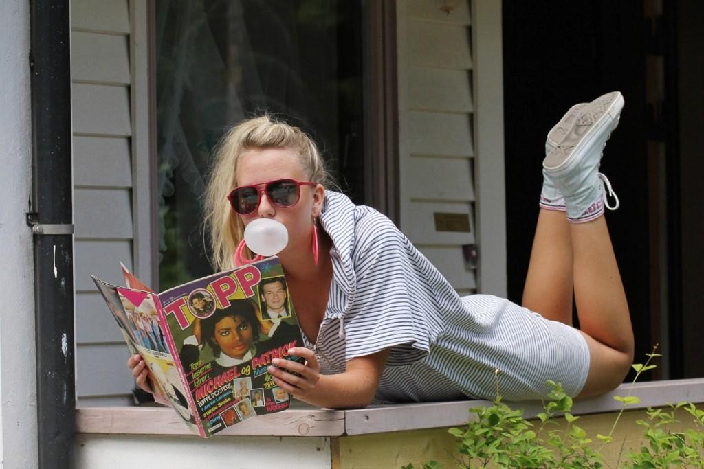 Ungjente leser ukeblad og blåser tyggegummiboble. Har solbriller og hestehale. Kul og tidsriktig 80-tall.