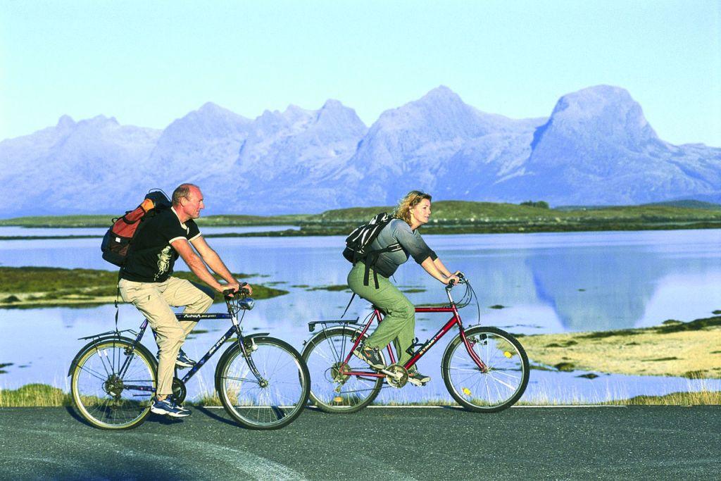 To personer på sykkeltur på Helgeland i Nordland med fjellkjeden De syv søstre i bakgrunnen.