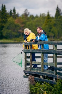 Mann og dame står på brygge og fisker. Han med stang mens hun holder i hoven.
