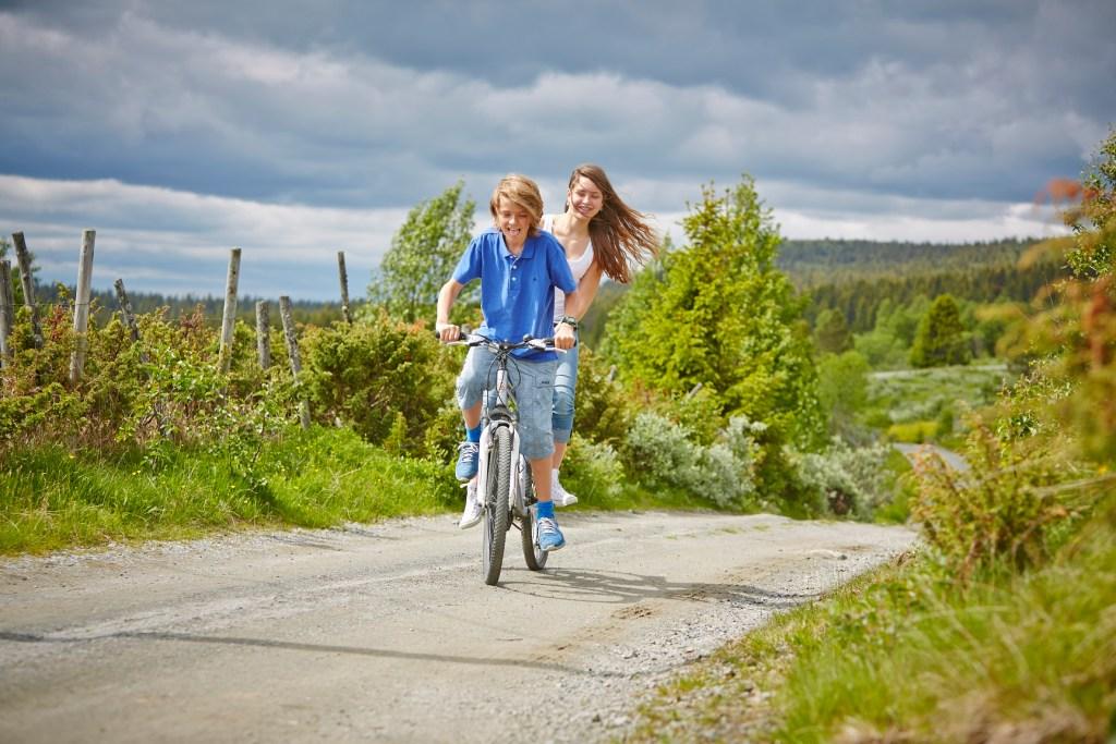 To ungdommer på samme sykkel sykler på grusvei på Golsfjellet.