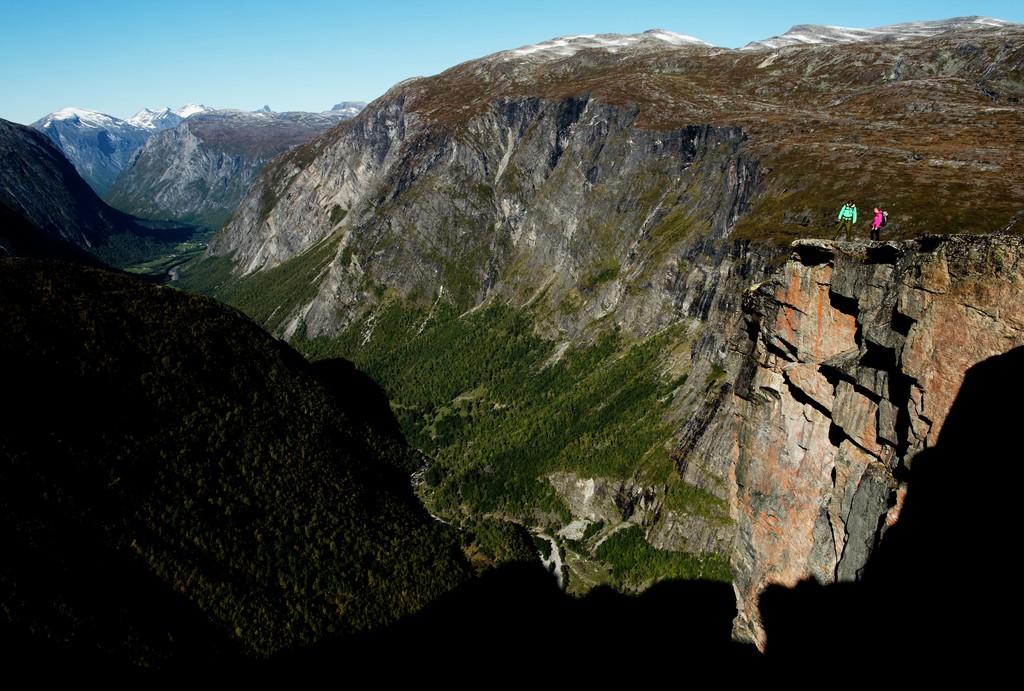 To personer i turklær står ute på en klippe og beundrer utsikten over Aursjøvegen i Sunndal.
