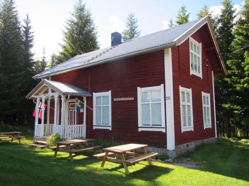 Rødmalt gammelt hus som inneholder Norske Grenselosers Museum i Eidskog. Norsk og svensk flagg vaier utenfor inngangen.