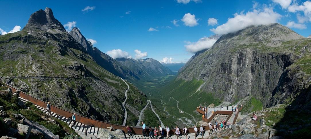 Et vidvinkel bilde som viser Trollstigen veien og utsiktsplattformmene på toppen. Masse turister som nyter utsikten. Det er sommer og blå himmel med noen få hvite skyter rundt fjelltoppene i bakgrunnen.