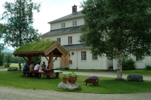 Hvitt hus og mennesker på benk