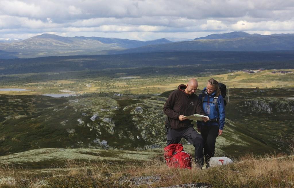 To personer ser på kart i fjellet