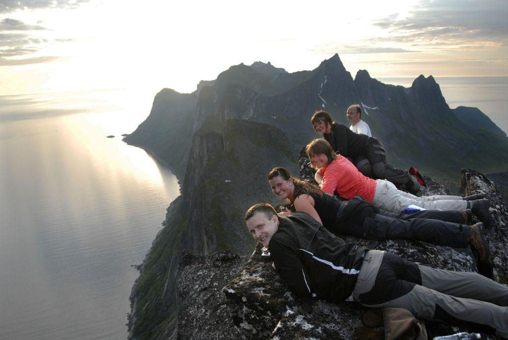 Personer på Senja ligger på magen på et fjell