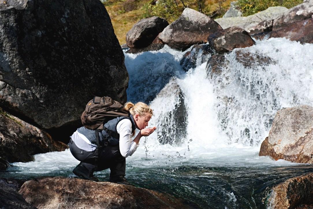 Kvinne med sekk drikker vann rett fra elven
