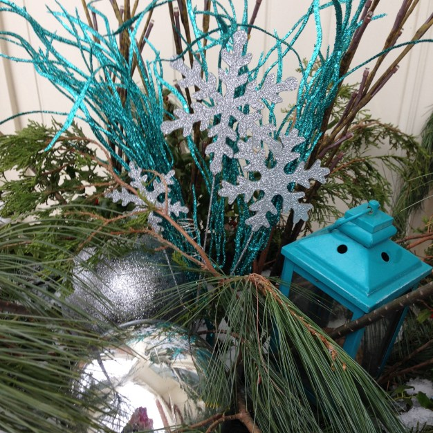 Sparkly stems, silver snowflakes , and silver bulbs all nestled among the pines.