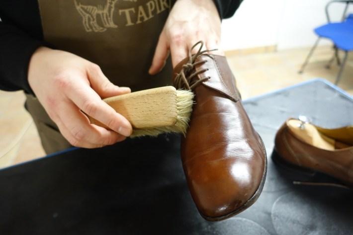 Mann hält Schuh und Bürste in der Hand und putzt