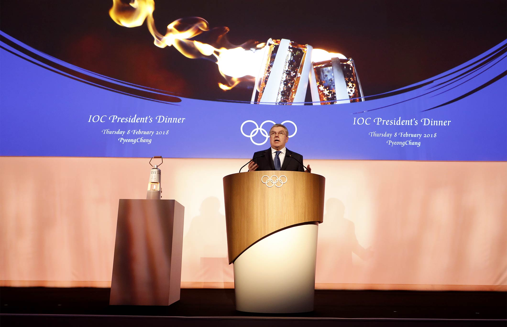 President Bach Hands The Olympic Torch To The United