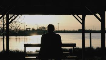 woman sitting on bench watching sun