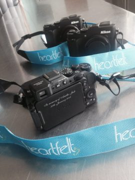 """Three cameras with light blue camera straps. The straps say Heartfelt, and the camera is engraved with """"In memory of Ariella Jade"""""""