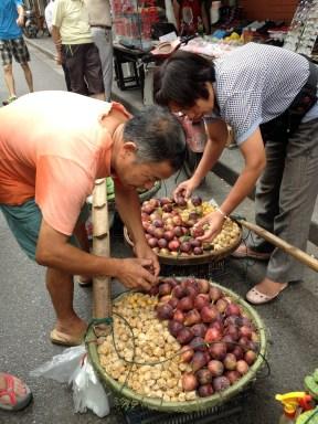 Street fruit vendor - he carries the fruit baskets from a long bamboo yoke.