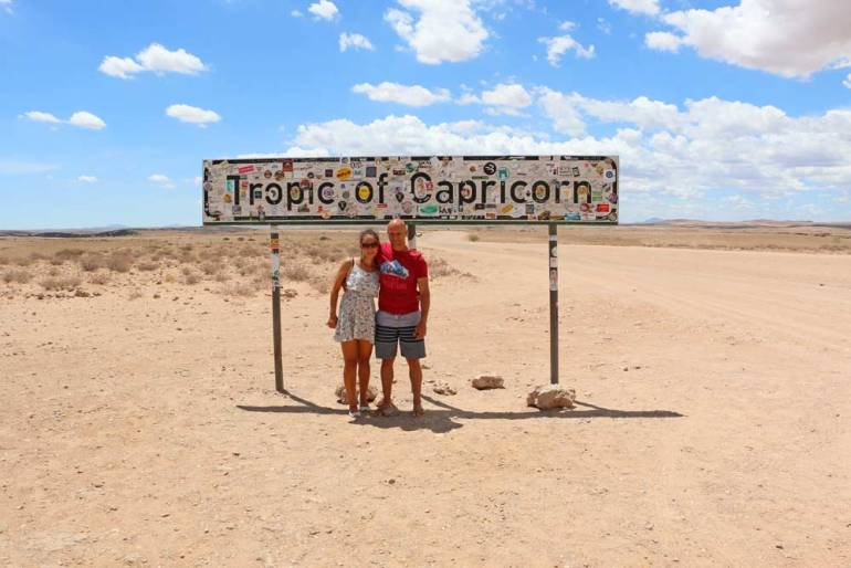 Campbell and Alya next to the Tropic of Capricorn sign in Namibia
