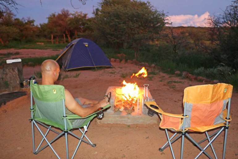 Campbell and a fire at night in a campsite in Namibia