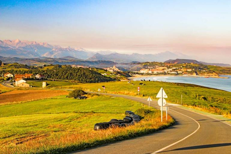 Green fields and hills, snow-peak mountains on the background, Camino del Norte, Spain