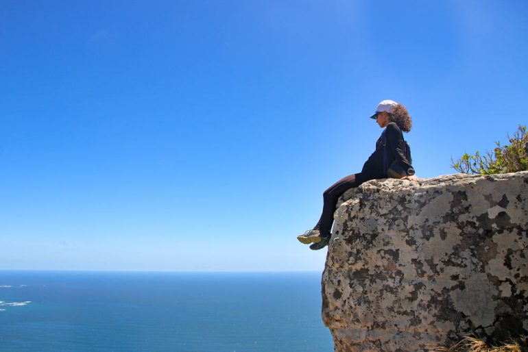 Alya on a massive rocky cliff enjoying the sea view form Lion's Head