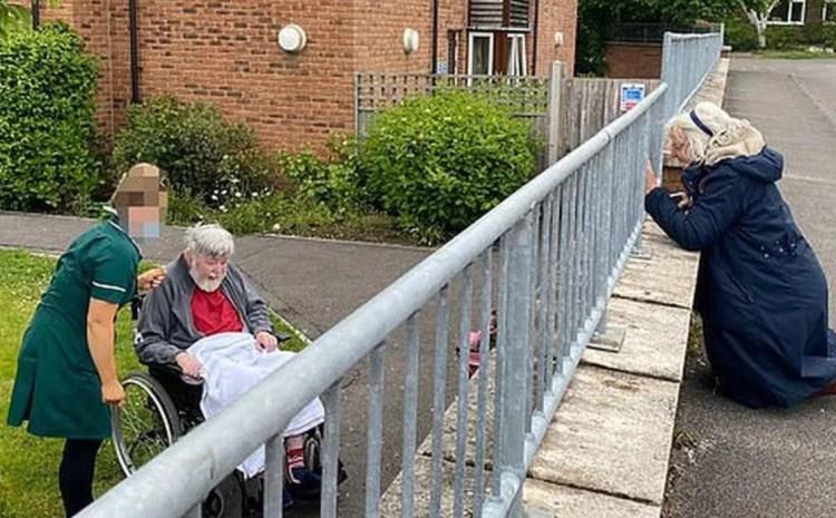 Poveşti de pandemie. O soţie iubitoare, surprinsă în timp ce îngenunchează pe stradă pentru a-şi revedea soţul aflat într-un centru de îngrijire.