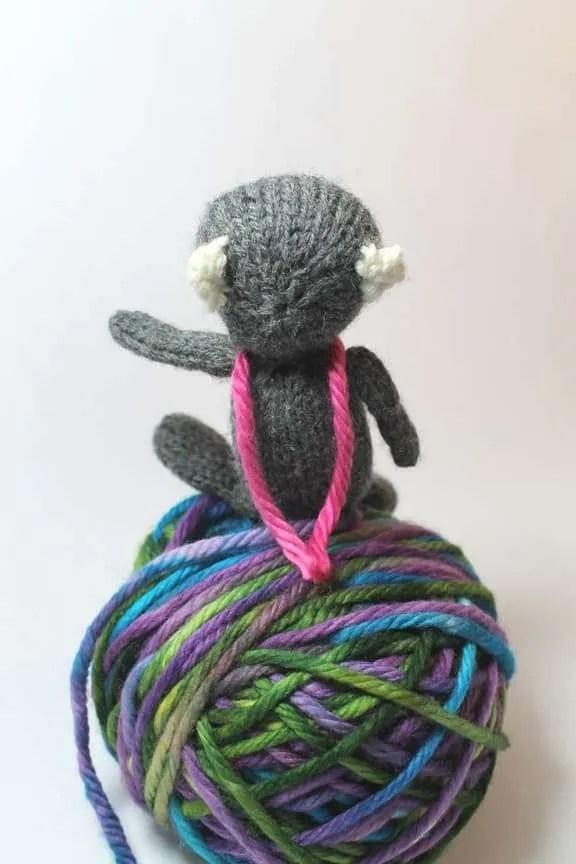 Little bear sitting backwards on a ball of yarn