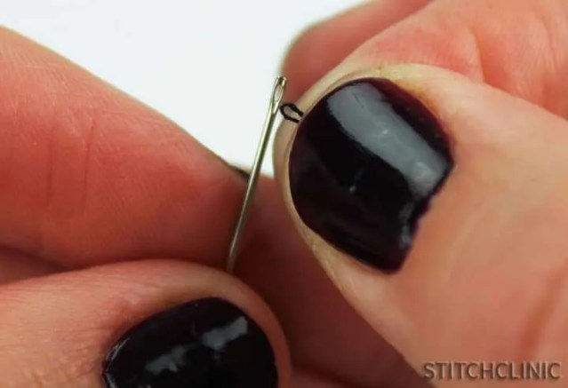 Putting looped thread through the eye of the needle