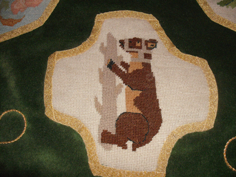 Detail of one of the needlepoint motifs - bear and ragged staff