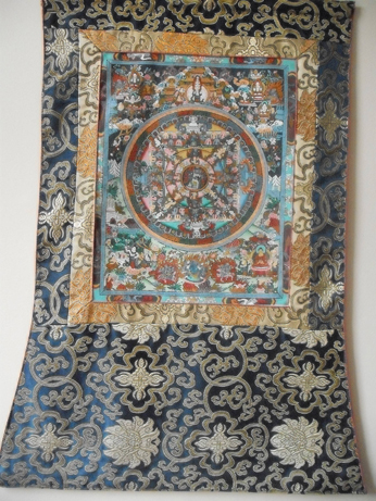 The thanka painting mounted in silk brocade