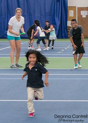 Child running on tennis court.