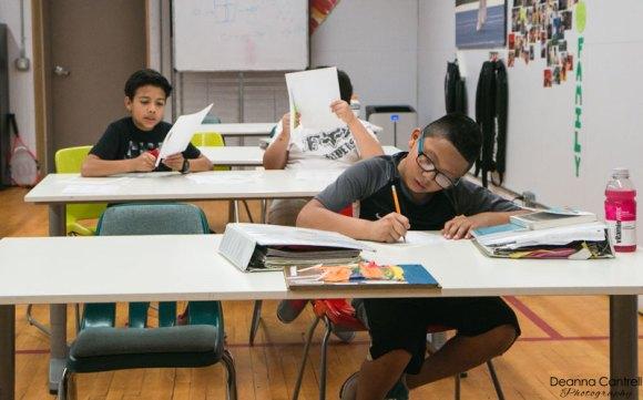 Three boys at desks in a classroom.