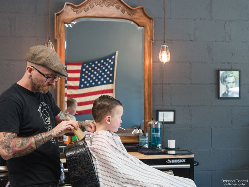 Barber styling the hair of a young boy.