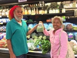 Starfish Market produce clerk Leslie Lambertis and Josephine Roller put a fresh bag of St. John-grown greens on the shelf.