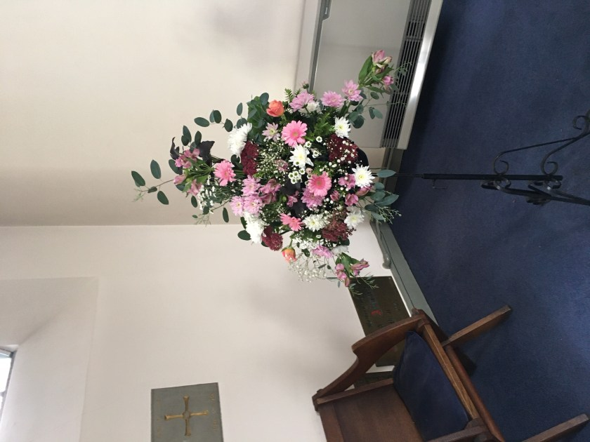 harvest flower arrangement next to the altar. Pinks, whites, deep reds with eucalyptus leaves