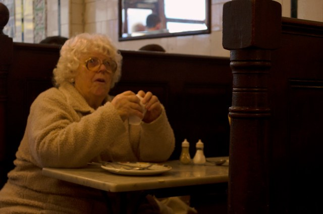An elderly woman sits alone in a booth having just finished her meal. Most of the shops customers are elderly and come alone