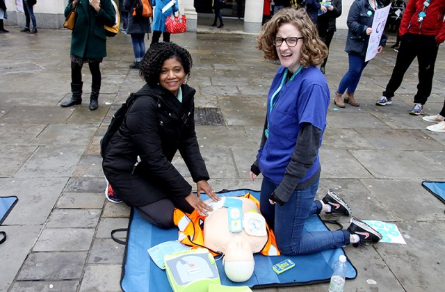 A passer-by learns how to administer CPR on a dummy with a defibrillator - which is available at all underground stations. Photo credit: Valerie Browne