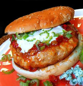 Recipe for Fiery Buffalo Chicken Burgers - Charge up your chicken burgers with a serious dose of hot sauce, cooled off with a dose of ranch dip to top.