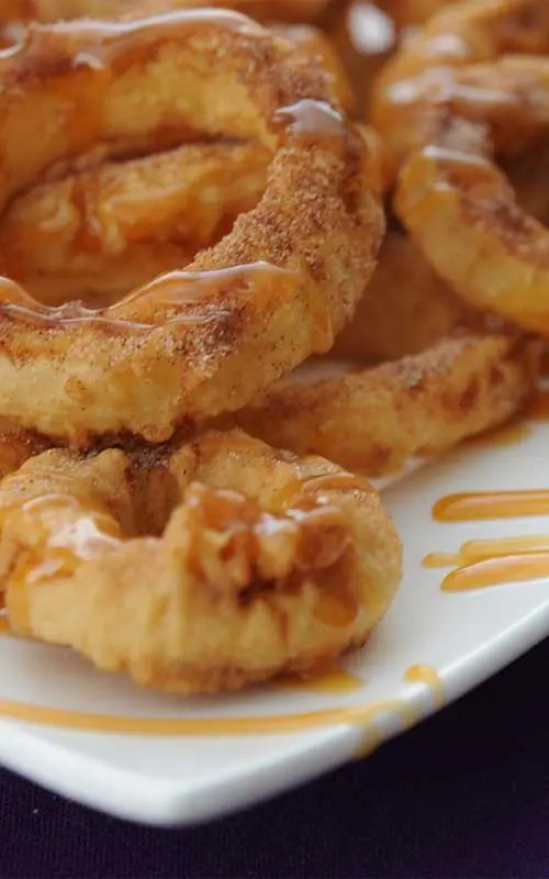 Recipe for Dessert Apple Rings With Cinnamon Cream Syrup - These crispy apple rings are warm and comforting on a cool fall day – and such a unique dessert! I love these sprinkled with cinnamon sugar and then drizzled with syrup.