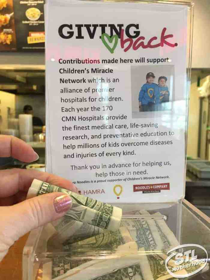 hand placing money in donation box for Children's Miracle Network