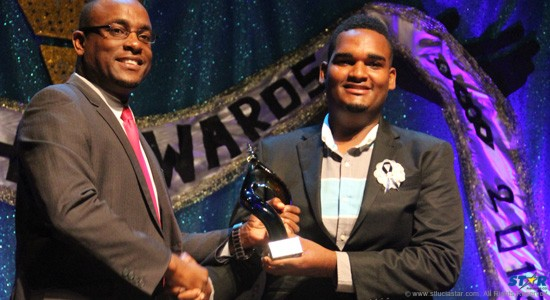 Tevin Shepherd(right) : Proud and humble as he receives the coveted Youth of the Year trophy from Shawn Edward, Minister for Youth.