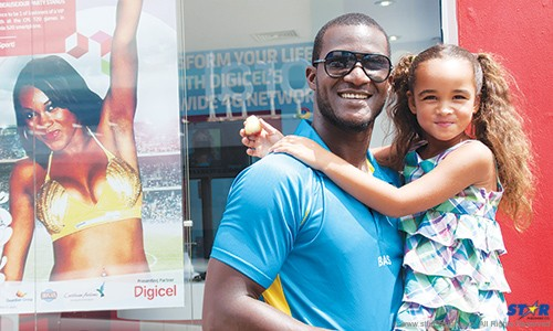 St Lucia Zouks Captain Darren Sammy and a young cricket fan outside the Digicel branch in Castries Wednesday.