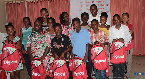 Digicel's cricket endorsee Johnson Charles with scholarship recipients.  Digicel's Country Manager Mrs. Siobhan James-Alexander addressing students.