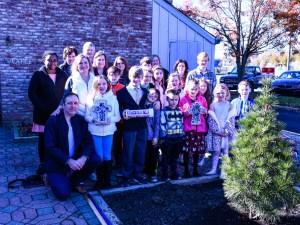 Group gathered around newly planted tree