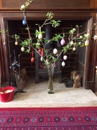 Fireplace with Easter eggs hung on tree branches in a vase