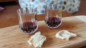 Two glasses of wine, and two pieces of bread set for communion on wooden board