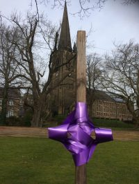 Large cross with ribbon on green in front of church