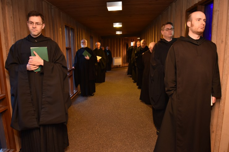 Monks waiting to pray Evening Prayer (Vespers) in the Cloister Walk.