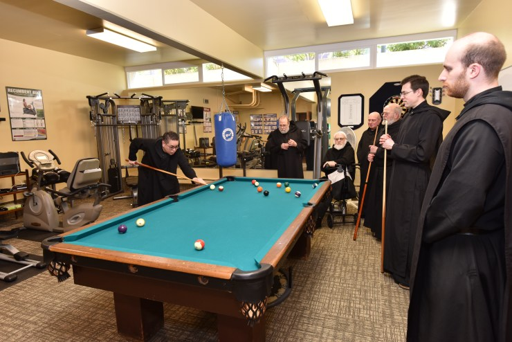 Monks playing billiards in the Monastery Game Room.