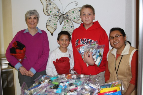 The SMS students made these blankets and scarfs as one of their school-wide service projects during Catholic Schools Week. Pictured are Sandra Miller, Mitchell Lee, Justin DeMond, and Ana Brown.