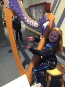 Grace playing the harp with no strings!