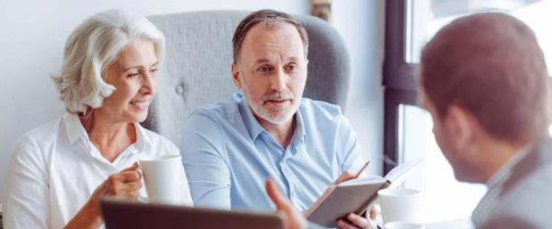 Positive older couple consulting with insurance agent